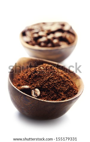 Wooden Bowls with coffee beans and ground coffee over white - stock photo