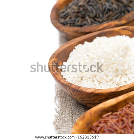 wooden bowls with uncooked rice, selective focus, close-up, isolated on white - stock photo