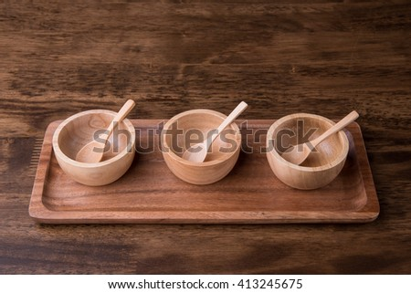 Wooden bowls with wooden spoon on wooden background - stock photo