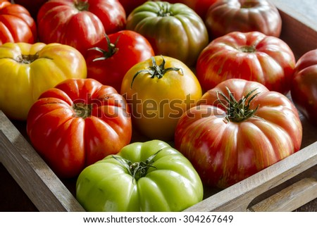 Wooden box filled with fresh vine ripened heirloom tomatoes from farmers market - stock photo