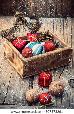 Wooden box filled with old fashion Christmas decorations.Photo tinted. - stock photo