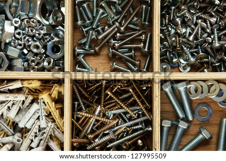 Wooden box for metal bolts, screws and nuts close up - stock photo