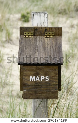 Wooden box that contains free maps year round for hikers, runners, cross-country skiers in recreational dune area in southwestern Michigan, USA - stock photo