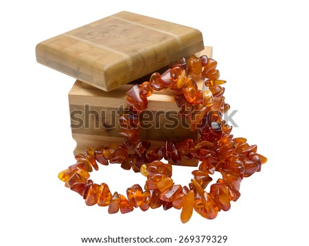 Wooden box with amber necklace isolated on white background - stock photo