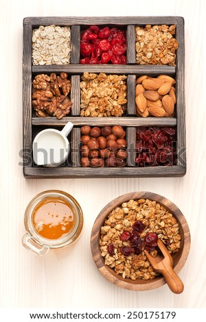 Wooden box with breakfast items - oats, granola muesli, nuts, honey, dried berries and milk. Top view. - stock photo