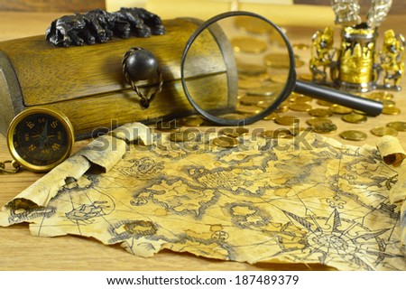 Wooden box with compass, magnifying glass and old map - stock photo