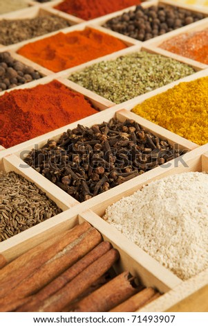 Wooden box with different herbs and spices - pepper, paprika, cumin and others. - stock photo