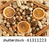Wooden box with different kinds of nuts, spices and dried oranges. Viewed from above. - stock photo
