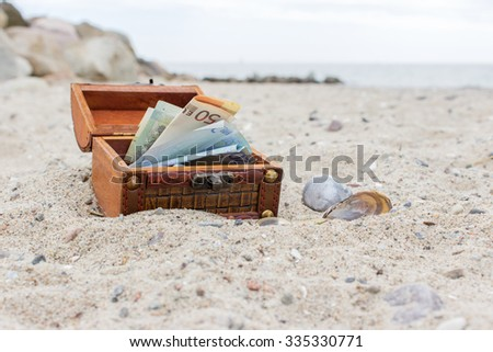 Wooden box with euro notes and coins in the sand / money / holiday budget  - stock photo