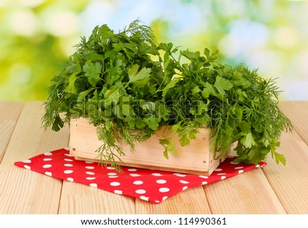 Wooden box with parsley and dill on wooden table on natural background - stock photo