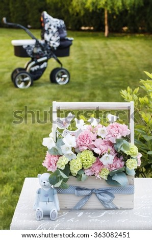 Wooden box with pink and yellow carnations, pram in the background