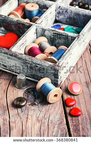 Wooden box with reels of sewing threads and buttons - stock photo