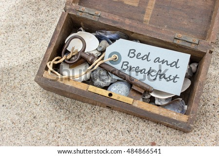 "Wooden box with shells, stones, keys and card with text ""bed and breakfast"" / bed and breakfast / beach holiday"