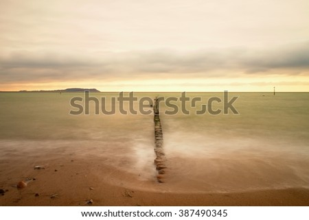 Wooden breakwater in wavy Baltic Sea. Romantic atmosphere at smooth wavy sea. Pink horizon with first hot sun rays. Dreamy effect - stock photo
