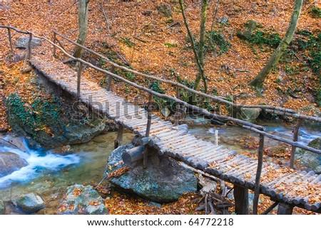wooden bridge across small river - stock photo