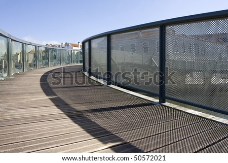 Wooden bridge and rails. A pathway into a urbanscape - stock photo