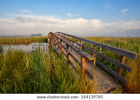 wooden bridge for bicycles through river in morning sunlight - stock photo