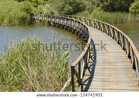 Wooden bridge in golf course lake  in Andalusia - stock photo