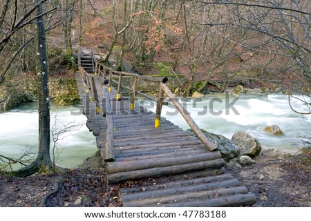 wooden bridge in mountain forest over stream - stock photo