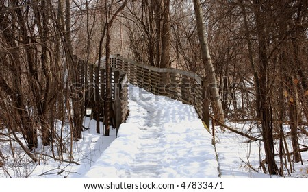 Wooden bridge in park with turn, winter scene - stock photo