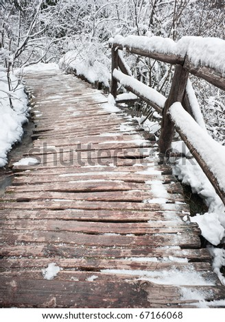 Wooden bridge in snow close-up. Winter forest of Plitvice national park, Croatia. - stock photo