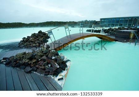 Wooden bridge in the Blue Lagoon geothermal bath resort in Iceland - stock photo
