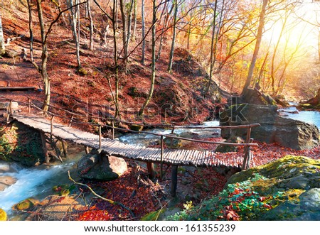 Wooden bridge in the mountain forest in autumn - stock photo