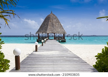 Wooden bridge leading to a thatched hut on a tropical island. Untouched tranquil beach and turquoise ocean. - stock photo