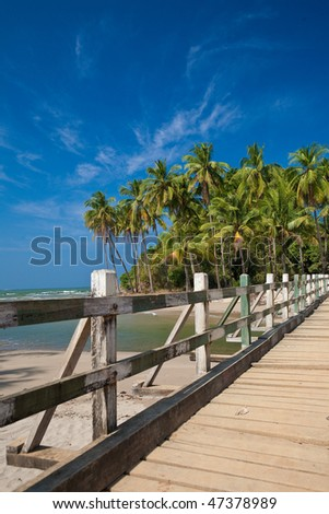 Wooden bridge leading to a tropical island lined with coconut trees along sandy beach. - stock photo