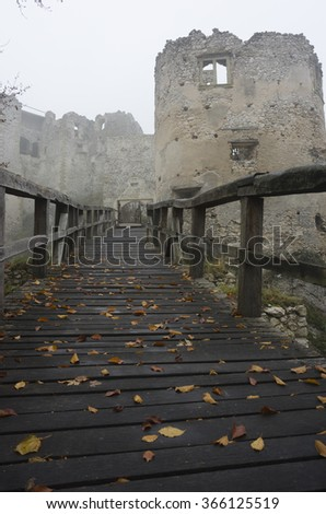 wooden bridge leading to an old mystical tower ruin in fog,mist - stock photo