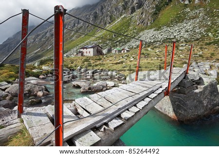 Wooden bridge on a mountain torrent at the top of a valley during fall. The bridge is near a mountain dew - stock photo