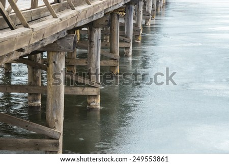 Wooden bridge on the frozen river - stock photo