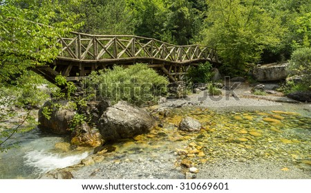 Wooden bridge over a mountain stream in the mountains of Olympus, Greece - stock photo