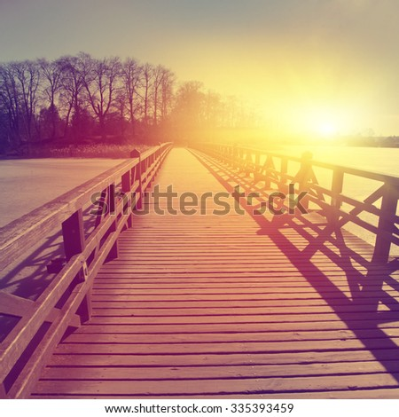 Wooden bridge over frozen river at sunset.  - stock photo