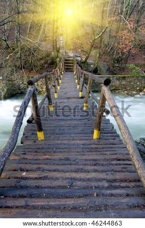 Wooden bridge over mountain river - stock photo