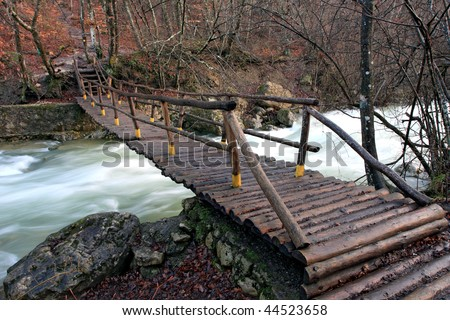 Wooden bridge over mountain river in autumn forest - stock photo
