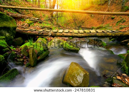 Wooden bridge over mountain stream in autumn forest - stock photo
