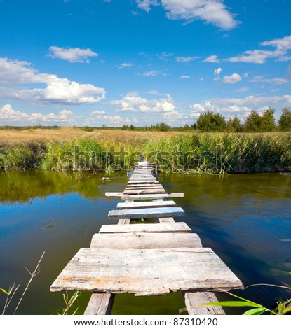 wooden bridge over river in steppe - stock photo