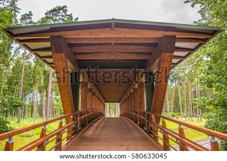 wooden bridge over the road in the park