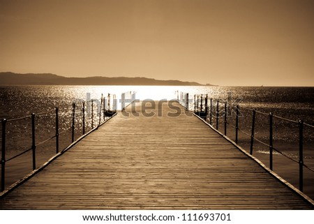 Wooden bridge to the sea - stock photo