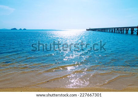 Wooden bridge to the sea in Koh Samui, Thailand. Glare on the blue sea water. Sandy beach and uninhabited islands. - stock photo
