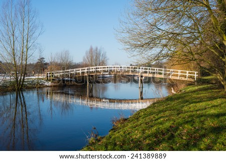 Wooden bridge with a white railing reflected in the mirror smooth water surface of a small river on a sunny day in the winter season. - stock photo