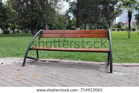 Wooden brown bench or seat against green grass in the park of Batumi