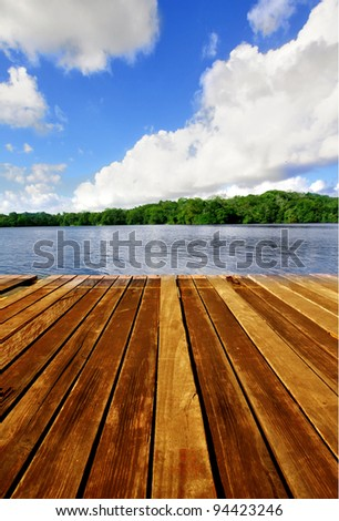 Wooden brown boardwalk on a lake with blue sky and clouds - stock photo