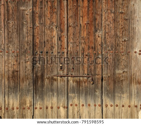 Wooden brown door. Timeworn background with rusty latch and padlock. Close up view with details.