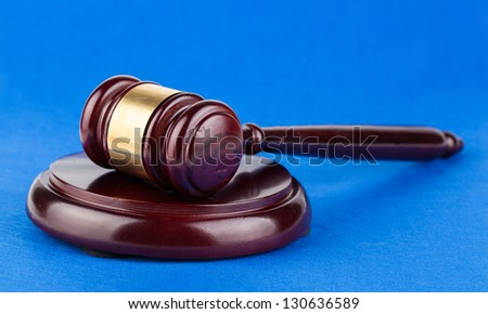 Wooden brown judges gavel on blue background - stock photo