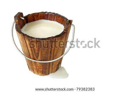 wooden bucket filled with fresh milk isolated - stock photo