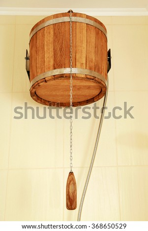 Wooden bucket for spa or sauna on the wall, selective focus - stock photo