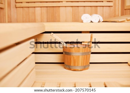 Wooden bucket of water and a ladle in a traditional wooden sauna for pouring onto the heated coals or heat source to produce steam - stock photo