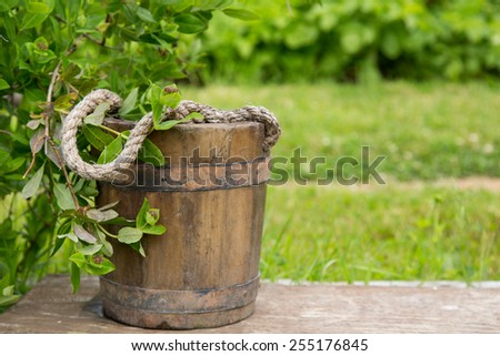Wooden bucket with rope inside on nature green background - stock photo